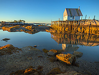 Stonington, Maine:<br /> Net shed and wharf on rock outcrop at low tide, Stonington Harbor