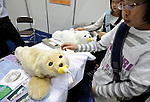 Young visitors stroke Paro, a seal-like robot developed by Intelligent Systems Research Institute for therapeutic purposes in hospitals, at Robo Japan 2008 in Yokohama, Japan on Saturday 09 October 2008.