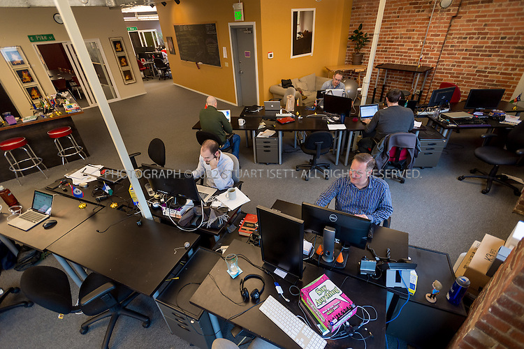 2/28/2014&mdash;Seattle, WA, USA<br /> <br /> Chris Hammersley, 42 (front right), a Seattle based e-commerce executive, working at his desk at Office Nomads, a coworking space in Seattle&rsquo;s Capitol Hill neighborhood.<br /> <br /> Hammersley is based in Seattle, but his company HQ is in Walnut Creek, Ca. and his bosses live in Chicago and Boston. When meetings take place, they can happen anywhere, so Chris uses coworking spaces in those cities and others when he travels for work. <br /> <br /> <br /> Photograph by Stuart Isett. <br /> &copy;2013 Stuart Isett. All rights reserved.
