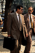 Sao Paulo, Brazil. Two businessmen in brown suits walking along the street.