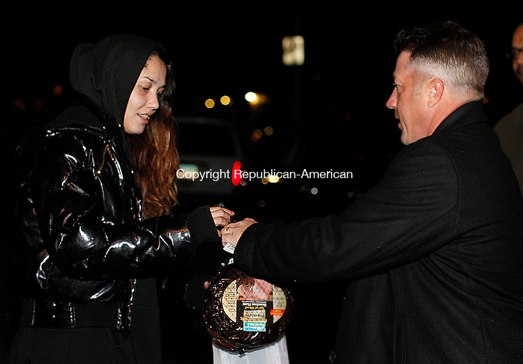 """Waterbury, CT-11 December 2012-121112CM03-  Joe Ventura, president of Positive Energy, right, hands a bag of food to Lucelis Valentino outside the Northwoods Apartments Tuesday night in Waterbury.  Ventura who grew up in the apartments, purchased the food items along with Guy Ferrialo the companies CFO.  This is the second year Ventura and his staff have distributed the items to the community.  Ventura said he's been fortunate to be able to give back to his old neighborhood.  """"It's about not forgetting where you came from."""" he said.  Ventura added he hopes the good gesture might inspire others.  The group handed out 50 bags which included a ham, canned vegetables soup and dessert.  The donated items were gone in less then 30 minutes.  Christopher Massa Republican-American"""