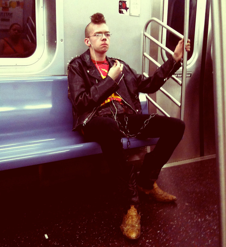 A young man sporting a punk style rides the New York subway.