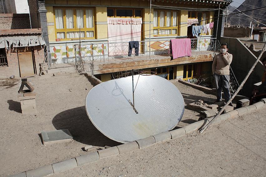 Tsering présente le convecteur solaire qui est placé sur la terrasse de sa maison, avec le support pour poser la bouilloire au centre, Xiahe decembre 2009