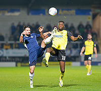 3rd December 2019; Pirelli Stadium, Burton Upon Trent, Staffordshire, England; English League One Football, Burton Albion versus Southend United; Stephen McLaughlin of Southend United does a high kick for the ball as Lucas Akins of Burton Albion comes in to kick the ball - Strictly Editorial Use Only. No use with unauthorized audio, video, data, fixture lists, club/league logos or 'live' services. Online in-match use limited to 120 images, no video emulation. No use in betting, games or single club/league/player publications