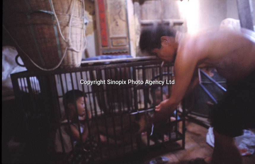 A boy called Qi Qi, 3 and 5 year-old Gwen Gwen are kept in a cage in a village house belonging to their uncle. The children's parents are both in prison and the uncle is too poor to afford child care for the children and are afraid they may be stolen and are afraid they may be stolen a common problem in China...PHOTO BY SINOPIX