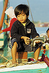 Young Cambodian boy holding fresh seafood sitting in the prow of a fishing boat on the Sanke river at dawn, Kampot, Cambodia.