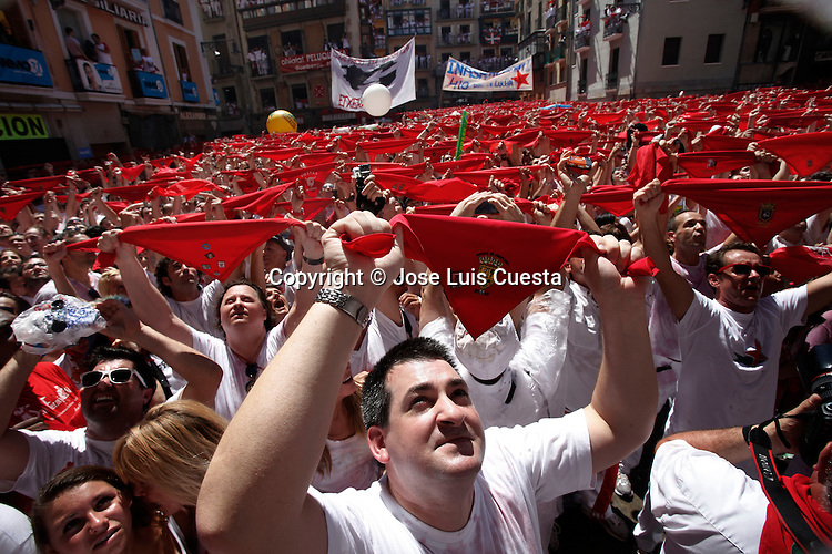 "People show their traditional red handkerchief on the first day of Sanfermines in city hall square, in Pamplona, northern of Spain. San Fermin starts with the launch of a rocket, which is known as ""chupinazo"". San Fermin festival is worldwide known because the daily running bulls."