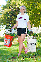 Kaitlyn Roberts,'20, hauls weeds as she volunteers at the Methodist Community Gardens in Middletown while taking part in the Salve Regina Service Plunge.