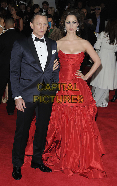 Daniel Craig, Berenice Marlohe.'Skyfall' Royal World Film Premiere, Royal Albert Hall, Kensington Gore, London, England..23rd October 2012.full length black strapless dress cleavage gathered hand on hip red tuxedo white shirt bow tie.CAP/CAN.©Can Nguyen/Capital Pictures.