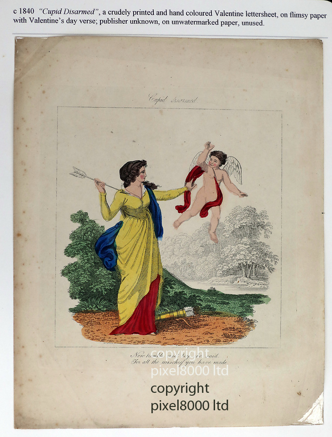 Pic shows: 1840 valentine card Cupid Disarmed<br /> <br /> <br /> Valentine's Cards  through the ages<br /> collection at an Exhibition in London today  13.2.19<br /> <br /> A selection of the world's oldest Valentine's Day cards are on display until 16th February at Stampex International, the UK's largest stamp collecting exhibition, at the Business Design Centre, Islington. Collected by Judith Holder over the last 50 years, some date back as far as 1720.<br /> <br /> <br /> Cards being held by Susan Wylie who is overseeing the exhibition <br /> <br /> <br /> <br /> <br /> pic by Gavin Rodgers/Pixel8000