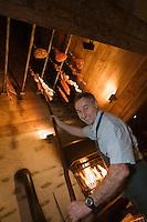 Europe/France/Rhone-Alpes/74/Haute-Savoie/ Chamonix:  Pierre Carrier acroche ses charcuteries de montagne dans la cheminée- fumoir  (Borne en Chamoniard) du Restaurant: La Maison Carrier