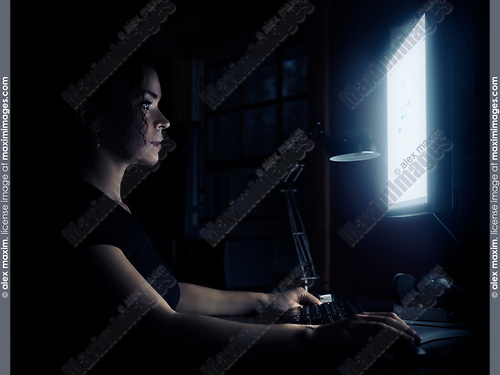 Young woman sitting at a desk in front of a computer with her face illuminated by the light of the monitor screen