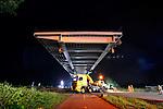 WEESP - In het holst van de nacht schuift de nieuwe de door ingenieursbureau Movares ontworpen en door bouwcombinatie KWS-Mercon gebouwde stalen Weesperbrug over één van de vier vrachtwagens die de pontons met tuibrug met kabels op zijn plek moeten houden in het Amsterdam-Rijnkanaal voor nauwkeurig plaatsen op de landhoofden van de oude - en verwijderde - Weesperbrug. De prefab in Gorinchem opgebouwde stalen boogbrug, is één van de vijf nieuwe bruggen die in opdracht van Rijkswaterstaat's project Kargo gebouwd worden, ter vervanging van verouderde bruggen en ter verhoging van de doorvaarthoogte voor vierlaagse containerschepen. De nieuwe brug is al  geasfalteerd, voorzien van leuningen en heeft straatlantaarn. COPYRIGHT TON BORSBOOM