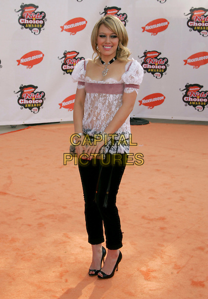 HILARY DUFF.Attends Nickelodeon's 18th Annual Kids' Choice Awards Show held at UCLA's Pauley Pavilion in Westwood, California, April 2nd 2005..full length black tight fitted trousers white lace top pink stripe Hillary clutch bag.Ref: DVS.www.capitalpictures.com.sales@capitalpictures.com.©Debbie VanStory/Capital Pictures