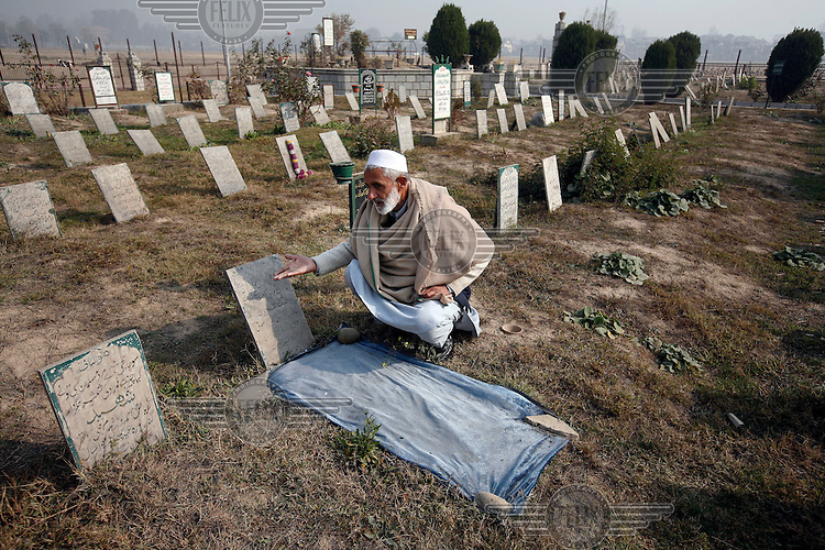 The caretaker of Iddgah martyrs' cemetary  reads from a toombstone on a grave. Around a thousand peole have been buried in this cemetary alone since 1989, after being killed by Indian security forces. Srinagar,Kashmir, India. © Fredrik Naumann/Felix Features