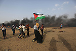 Palestinian protesters gather during clashes with Israeli security froces in a tent city protest where Palestinians demand the right to return to their homeland and against U.S. embassy move to Jerusalem at the Israel-Gaza border, in Khan Younis in the southern Gaza Strip on May 25, 2018. Photo by Ashraf Amra