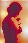 silhouette of woman smelling flower