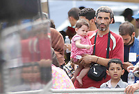 Operazione Mare Nostrum , immigrati in scendono al porto di Napoli dalla nave Virginio Fasan, impiegata nell operazione Mare Nostrum <br /> una famiglia in attesa di conoscere la propria destinazioneMigrants  disembark in Naples Harbour <br />  from the ship &quot;Virginio Fasan&quot; of the Italian navy,  the  vessel involved in search-and-rescue operations the ship is engaged in the rescue operation &quot;Mare Nostrum&quot; in the Mediterranean Sea