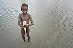 A boy holds a fish he caught in Poktap, a town in South Sudan's Jonglei State where conflict, drought and inflation have caused severe food insecurity.