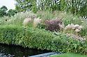 Bridge Over Troubled Water show garden, designed by Anoushka Feiler, Hampton Court Flower Show 2012. Plants include: Astilbe 'Red Sentinel', Calamagrostis x acutiflora 'Karl Foerster', Cenolophium denudatum, Deschampsia cespitosa 'Pixie Fountain', Dianthus carthusianorum, Dianthus cruentus, Erigeron karvinskianus, Hordeum jubatum, Pennisetum orientale 'Tall Tails', Pennisetum setaceum 'Rubrum', Pennisetum thunbergii 'Red Buttons',