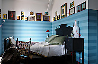 A dramatic black-painted bed is surrounded by blue striped walls and lined with antique family photographs
