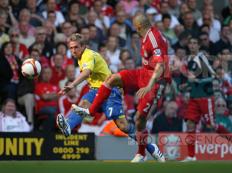Liam Lawrence of Stoke City in action with Andrea Dossena of Liverpool.