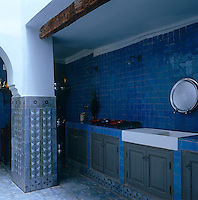 The walls of the kitchen are decorated with blue tiles matched with steel grey cupboards and a hand-painted tiled floor