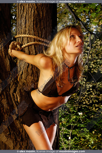 Woman in ragged clothes tied with ropes to a tree in a forest