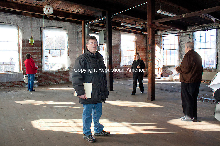 WINSTED CT- DECEMBER 13  2012 -121312DA15- Marrty Goldin, Owner of the former Winsted Furniture building at 10 Bridge St. in Winsted is now the Complex Mad River Lofts, gives a tour of one of the many rooms that will be renovated for possible artist studios, high-end tech offices, light manufacturing and restaurants..Darlene Douty Republican American