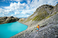 Trail running above the turquoise water of the Wildsee, below the Pizol, Switzerland