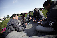 Pictured: A group of male refugees play card games on the ground Thursday 25 February 2016<br /> Re: Refugees have been left stranded in temporary camps after Greek FYRO Macedonian borders were closed in Idomeni, northern Greece.