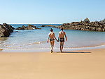 Couple holding hands on beach walking into sea, Praia dos Alterinhos, Zambujeira do Mar,  Portugal, Southern Europe
