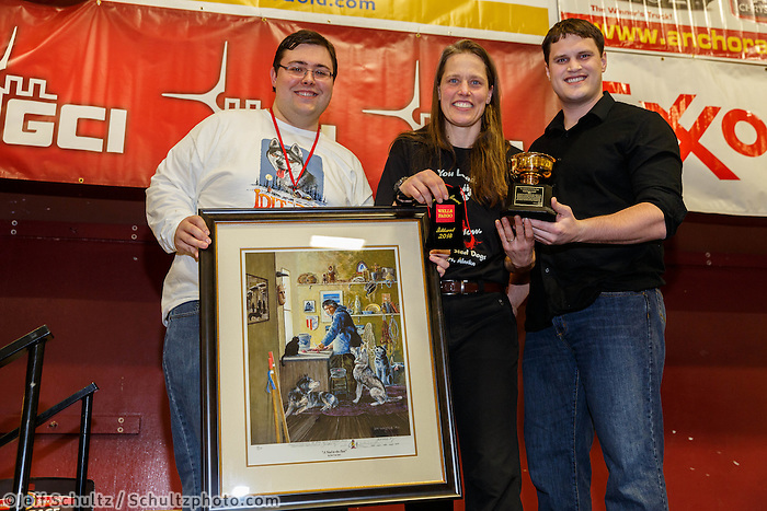 Jake Slingsby and Scott A. Johnsn present Aliy Zirkle with teh Wells Fargo Bank Alaska Gold Coast Award at the musher 's finishers banquet in Nome on Sunday March 16 after the 2014 Iditarod Sled Dog Race.<br /> <br /> PHOTO (c) BY JEFF SCHULTZ/IditarodPhotos.com -- REPRODUCTION PROHIBITED WITHOUT PERMISSION