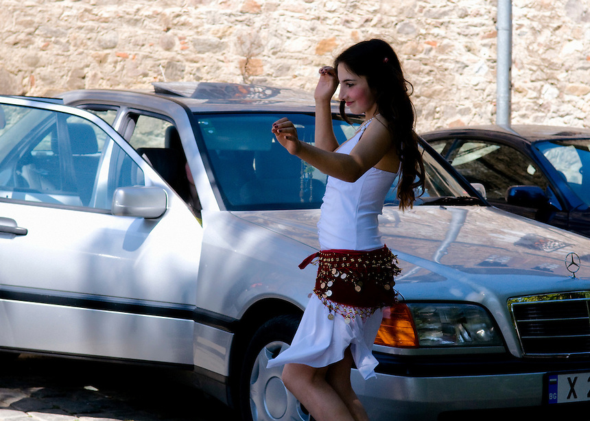 "Donka Angelova, 13 from Stambolovo, Haskovo area, belly dancing in front of her father's Mercedes. She and her 3 sisters came to the Bachkovo monastery for the traditional ""bride market"" that take place here on the day of  the Assumption of the Virgin Mary. Though not of an age for marriage, Donka attracted many young men to watch her dancing."