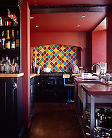 This galley kitchen is painted a dark red with a geometric pattern of colourful tiles above the cooker