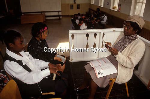 Sunday school children  Bible study. Church of God  of Prophecy West London UK.  from A STORM IS PASSING OVER a Look at Black Churches in Britain. Published by Thames and Hudson isbn 0 500 27826 1