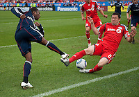 22 May 2010: New England Revolution midfielder Sainey Nyassi #14 battles with Toronto FC defender Dan Gargan #8 during a game between the New England Revolution and Toronto FC at BMO Field in Toronto..Toronto FC won 1-0.....