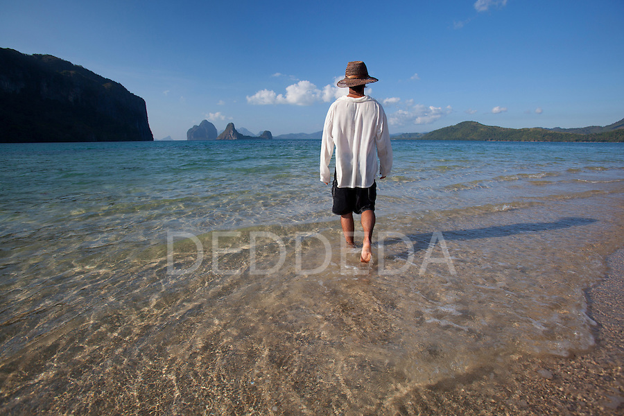 A male tourist walks along the white sand on a small island near El Nido, in the famous and beautiful Bacuit Archipelago in Palawan, Philippines.