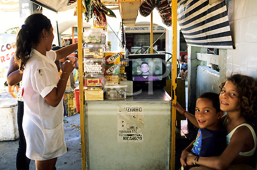 Bahia State, Brazil. Market stall selling sweets, chewing gum and snacks with a Philco portable television.