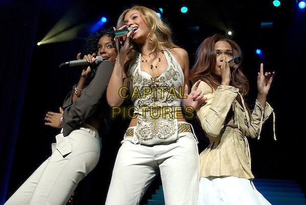 DESTINY'S CHILD.KELLY ROWLAND, BEYONCE KNOWLES & MICHELLE WILLIAMS.Perform at 100.3 The Beat Holiday Cooldown 2004 Concert held at The Universal Ampitheatre in Universal City, California, USA, December 15th 2004..half length stage concert gig music singing gold beaded halterneck silver beads pearls flower necklace brooch broach jewelled top belt necklace.Ref: DVS.www.capitalpictures.com.sales@capitalpictures.com.©Capital Pictures.