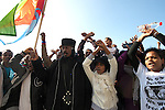 A priest waves the Eritrean flag as African asylum-seekers protest in front of the US Embassy in Tel Aviv, Israel, calling the US to help them receive recognition from the Israeli government as refugees.
