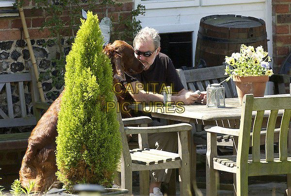 GEORGE BEST.In the garden of ex-wife Alex Best's home in Lower Kingswood, Surrey, June 9th 2005..half length sitting table drinks sunglasses gin and tonic  ex-husband dog pet.Ref: FIN.www.capitalpictures.com.sales@capitalpictures.com.©Steve Finn/Capital Pictures.
