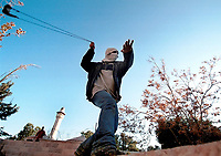 With a minaret seen in the background, a Palestinian youth uses his slingshot to hurl a stone at Israeli forces during clashes in east Jerusalem's Old City following noon prayers Friday Dec. 22,2000. Photo by Quique Kierszenbaum