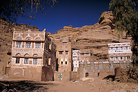 Decoratively painted towerhouses stand at the base of a rock formation. Thilla, Yemen.