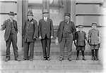 COURTHOUSE DENIZENS, C. 1915. The north steps of the post office are the setting for this group portrait, which includes a policeman and two newsboys. Mirrored in the glass doors is a sign for Deluxe Studio, a photographer's establishment north across P Street from the courthouse. John Johnson's care in composing images suggests he was probably aware of this reflection.<br />