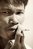 INDONESIA, Mentawai Islands, Kandui Resort, close-up of mid adult man smoking cigarette (B&W)