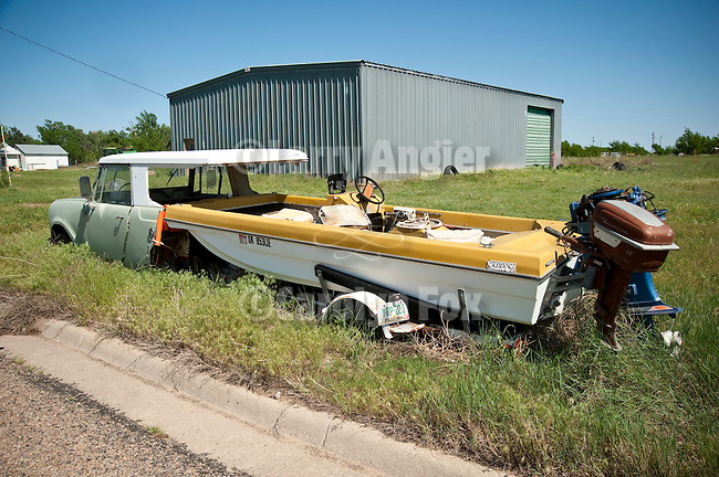 Combo-car: an International Scout grafted onto a boat trailer with boat attached along the highway in the Texas Panhandle.