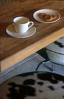 A coffee cup and saucer on the chunky kitchen table with chairs upholstered in cow hide