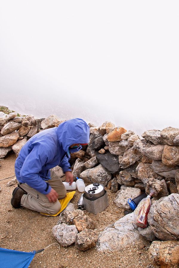 Man preparing stove in backcountry camp on the Lower Saddle of the Grand Teton, Grand Teton National Park, Teton County, Wyoming, USA