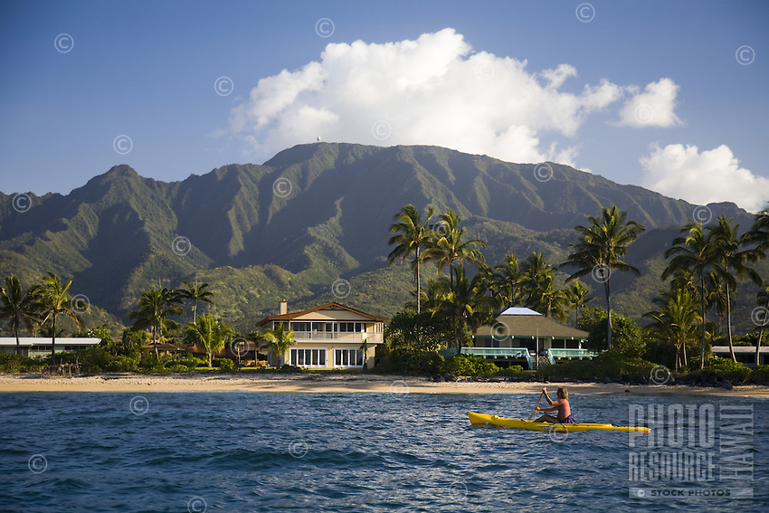 Man paddling a yellow kayak off the shore of Waialua, with houses, palm trees and Mount Kaala in the background